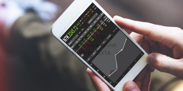 スマホで株価チェック | Photo by PIXTA